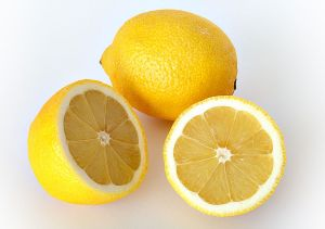 A whole lemon and a sliced lemon, white background