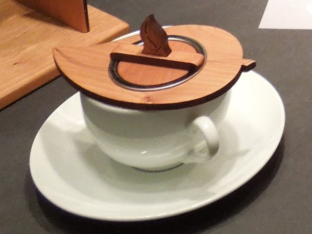A tea infuser in a teacup, with a wooden lid