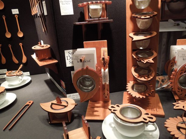A display of tea infusers with wooden holders and a metal mesh
