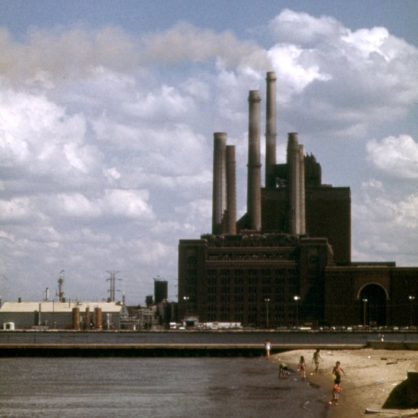 A coal fired plant, with big smokestacks, and a lake and beach in the foreground