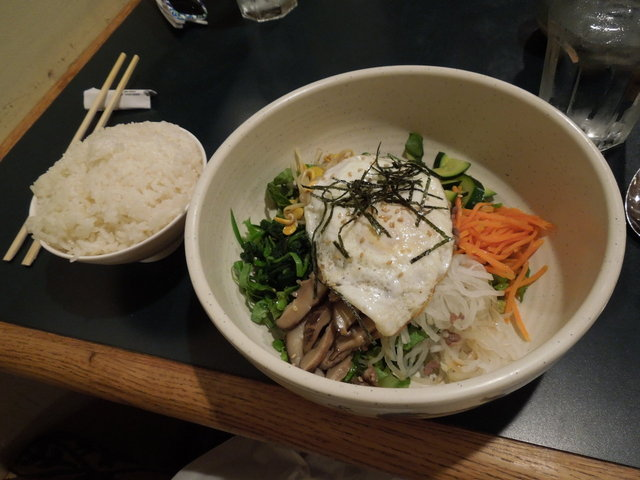 A bowl of rice and a bowl of bibimbap, showing mixed vegetables, and an egg, with grated seaweed on top
