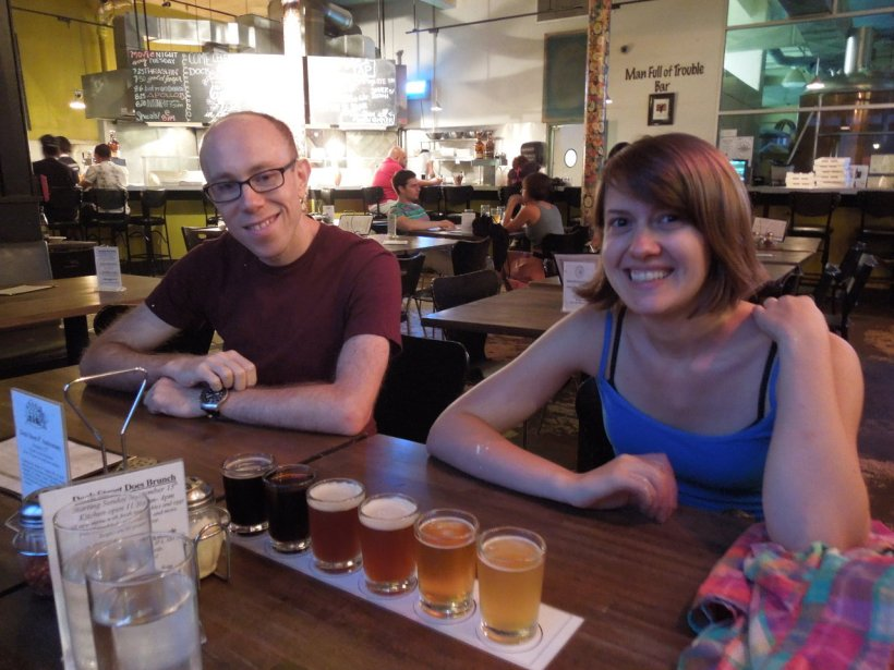 An attractive young man and young woman sitting in a brewpub in front of a sampler of six beers of different colors ranging from dark to light
