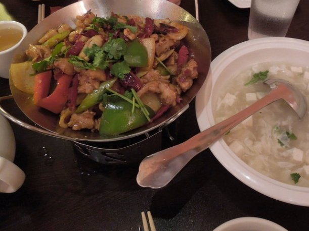 A bowl of Sichuan dry pot, with mixed vegetables and chicken in a metal bowl, and a white bowl of seafood tofu soup