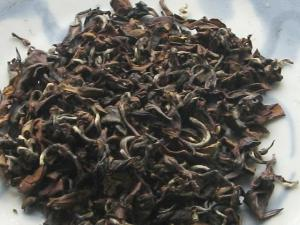 A dark loose-leaf oolong tea, with curved leaves